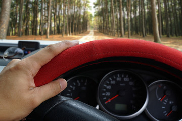 Driver's hand on the steering wheel inside of a pickup truck