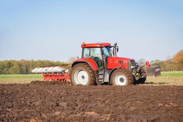Ackerbau, roter Traktor mit rotem Pflug bei der Bodenbearbeitung