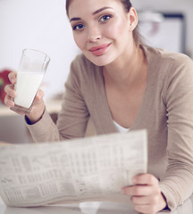 Happy young woman having healthy breakfast in kitchen