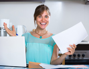 Smiling woman with documents at kitchen.
