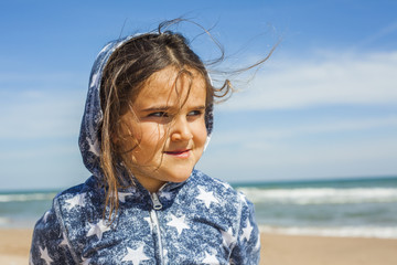 Close up smily girl posing in the beach in a windy day in Easter