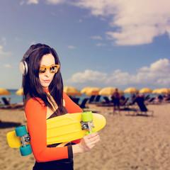 Junge Frau mit einem Skateboard posiert