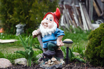 Statue of gnome with red hat in garden