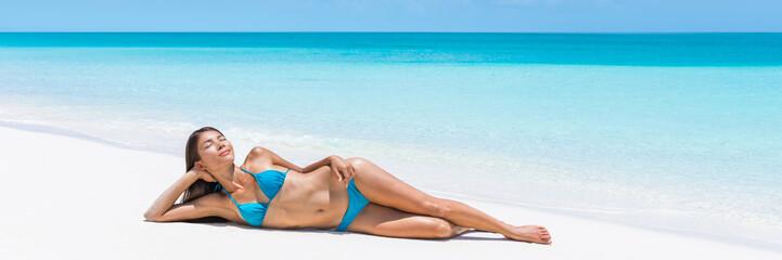 Wall Mural - Caribbean turquoise ocean getaway beach destination lady dreaming on perfect white sand. Paradise tropical travel destination. Asian blue bikini woman lying down relaxing sun tanning laid back.