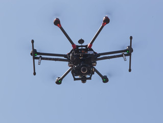 quadrocopter with camera flying in sky