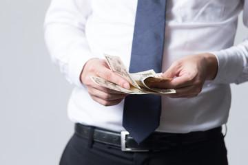 一万円札を持つ男性サラリーマン(白バック)