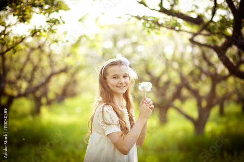 Girl with a bouquet of dandelions in the garden