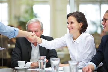 Geschäftsleute beim Hände schütteln im Meeting