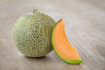 Melon with slices and on a wooden table