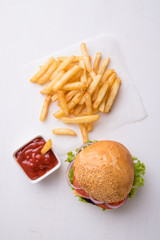 hamburger on white table with fries