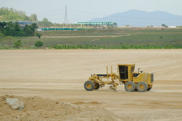 Yellow bulldozer in a field of sand