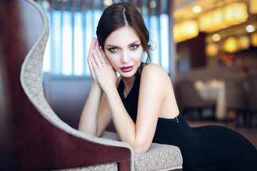 Beautiful young woman in black evening dress posing in interior.