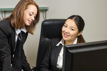 Two young businesswomen using pc