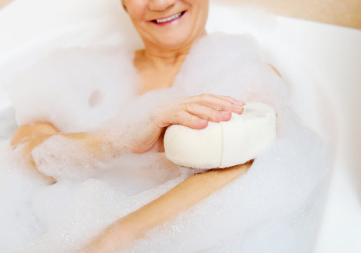 Bathing woman relaxing with sponge