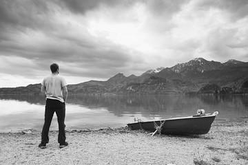 Adult man in blue shirt walk at old fishing paddle boat at mountains lake coast. Vintage photo effect