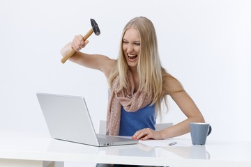 Angry woman attacking laptop computer