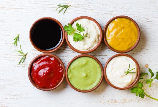 Sauces ketchup, mustar, mayonnaise, wasabi, soy sauce in clay bowls