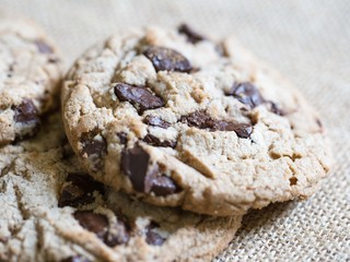 Chocolate chip cookies on brown cloth background with hazelnuts.
