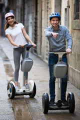 Young couple driving segways .