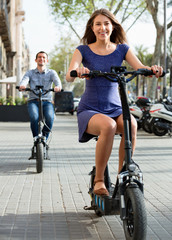 Happy young man and woman with electrkc bikes