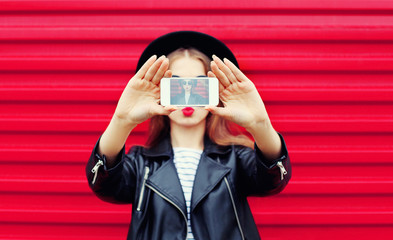 Fashion glamour woman makes self portrait on smartphone blowing