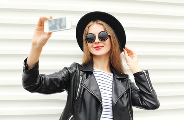 Fashion happy woman makes self portrait on smartphone in black r