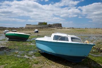 Bateaux en cale sèche devant un fort pendant la marée basse en Bretagne