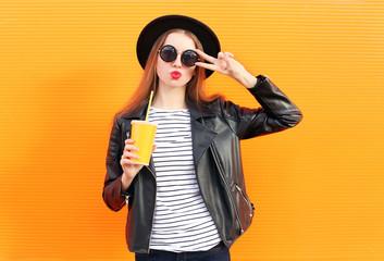 Fashion pretty woman in black rock style having fun over orange Wall mural