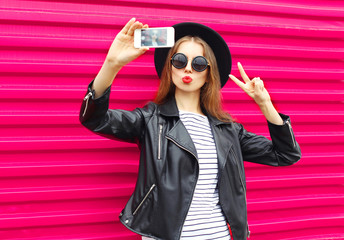 Fashion pretty woman makes self portrait on smartphone in black