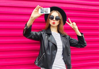 Fashion pretty woman makes self portrait on smartphone in black