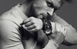 Advertising wrist watch concept. Beautiful (handsome) muscular male model with perfect body in grey jumper. He bites and unfastens the bracelet from the clock. Street style. Black and white