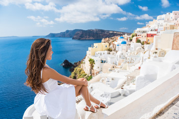Wall Mural - Europe summer travel destination Santorini tourist woman on vacation relaxing. Asian girl in white dress visiting the streets of the famous white village Oia with the mediterranean sea and blue domes.