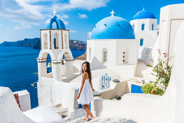Wall Mural - Santorini travel tourist woman on vacation in Oia walking on stairs. Lovely girl in white dress visiting the famous white village with the mediterranean sea and blue domes. Europe summer destination.
