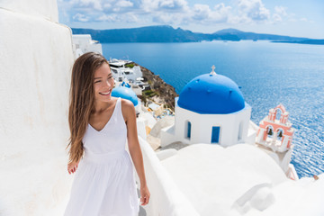 Fototapete - Santorini travel tourist woman on vacation in Oia walking on stairs. Person in white dress visiting the famous white village with the mediterranean sea and blue domes. Europe summer destination.