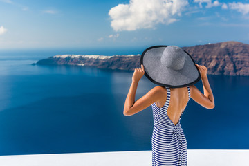 Wall Mural - Europe summer vacation travel destination luxury living woman looking at view of Mediterranean Sea and Santorini island Oia village. Elegant tourist lady in fashion back dress and floppy sun hat.