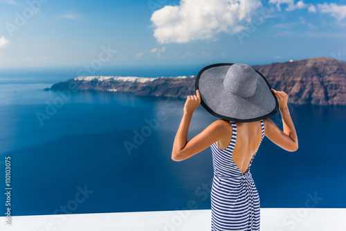 Wall mural Europe summer vacation travel destination luxury living woman looking at view of Mediterranean Sea and Santorini island Oia village. Elegant tourist lady in fashion back dress and floppy sun hat.