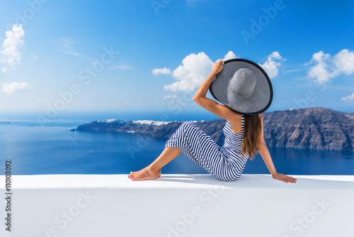 Wall mural Europe summer vacation travel cruise destination luxury living woman relaxing on outdoor terrace looking at view of Mediterranean Sea and Santorini Oia. Elegant tourist lady in fashion beachwear.