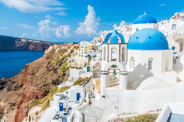 Greece famous touristic travel destination Santorini greek island. Three blue domes. Popular summer luxury vacation Europe cruise stop. Streets of European white village with the mediterranean sea.