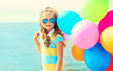 Portrait of happy smiling child on summer beach with colorful ba
