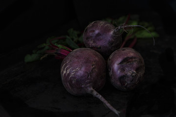 Three organic beets with leaves directly from the patch in a dark barn