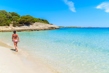 Unidentified attractive young woman in swimsuit walking along beautiful Petit Sperone beach on Corsica island, France