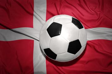 black and white football ball on the national flag of denmark