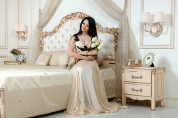 Stylish girl in sexy dress sitting on the bed