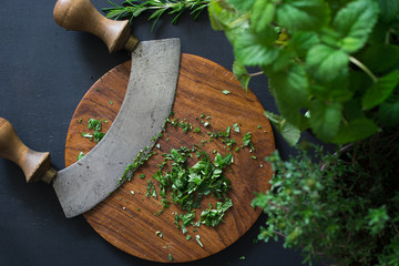 Aromatic herbs chopped with mezzaluna knife on wooden cutting board