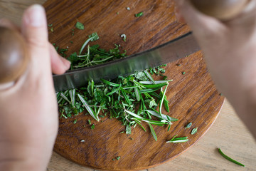 Chopping aromatic herbs with italian mezzaluna knife. Selective focus.