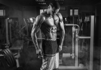 Strong athletic man with muscular body in gym.