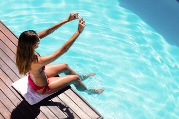 Woman taking a selfie on the pool edge