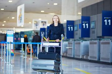 Fototapeta Young female traveler in international airport