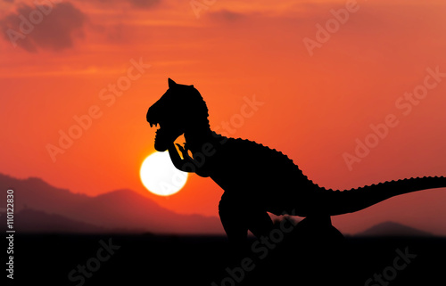 Silhouette of dinosaur sunset background