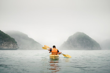 Couple paddling the kayak in mist weather